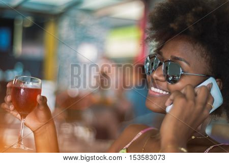 Happy african american young woman in cafe of Rio de Janeiro calling on smartphone and holding glass of red wine