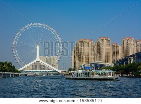 Tianjin,China - October 5,2016 : Cityscape of Tianjin ferris wheelTianjin eyes with tourist boat;selective focus at ferris wheel. Most modern popular landmark in Tianjin city China.