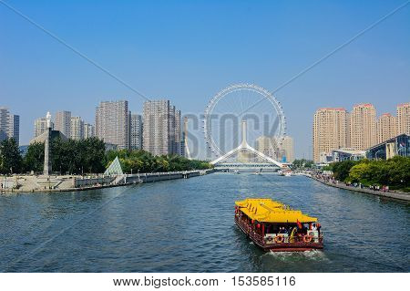 Tianjin,China - October 52016 : Cityscape of Tianjin ferris wheelTianjin eyes with tourist boat;selective focus at ferris wheel. Most modern popular landmark in Tianjin city China.