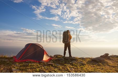 Sunrise in camping day. Backpacker man stands near tent and enjoy beautiful view.