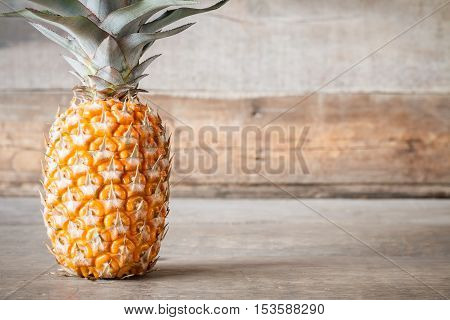 single ripe pineapple on wooden background with copyspace