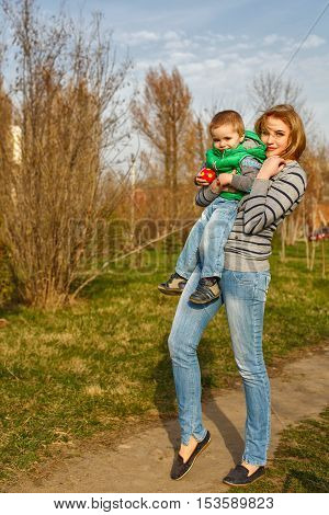 Mum holds on hands of the her son in the autumn park. Family time. Happiness of childhood and motherhood. Outdoor Activities.
