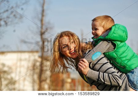 Mom rolls her son on his shoulders in autumn park. Family time. Happiness of childhood and parenthood. Outdoor Activities. Piggyback