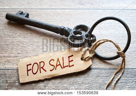 Old key with paper label - For sale text - on wooden background. Real Estate Concept.
