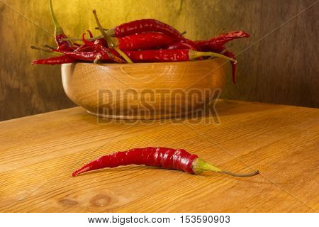 Chili in wooden plate on a wooden background