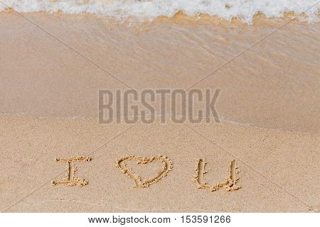 I love you - the inscription on the sand beach with a soft wave