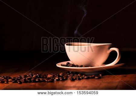 A cup of coffee placed on a wooden table with roasted beans scattered around, is selectively illuminated to produce a high contrast in the image. A thin wisp of smoke coming out of the cup provides warmth and elegance to this photograph.