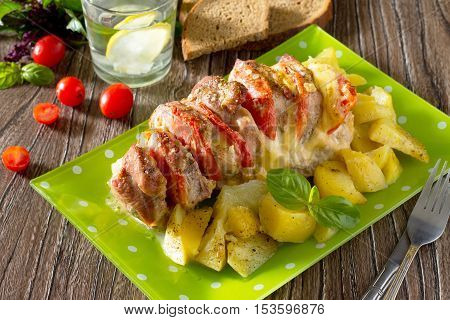 Baked Meat With Cheese And Tomato With Baked Potatoes On A Wooden Table.