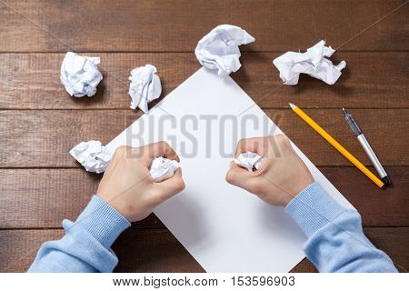 Man crumpling paper while writing notes on wooden table