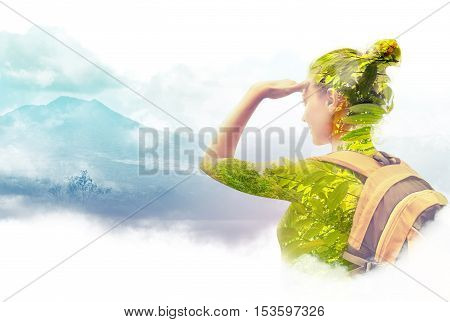 Double exposure portrait of young woman traveler looking at Batur volcano. Indonesia.