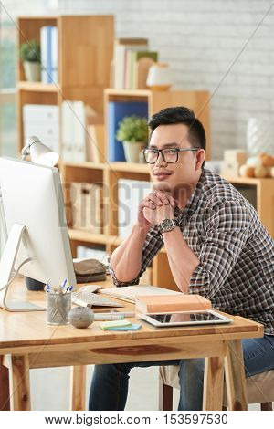 Smiling Vietnamese businessman sitting at table with computer and looking at camera