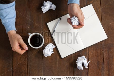 Man crumpling paper while having cup of coffee on wooden table