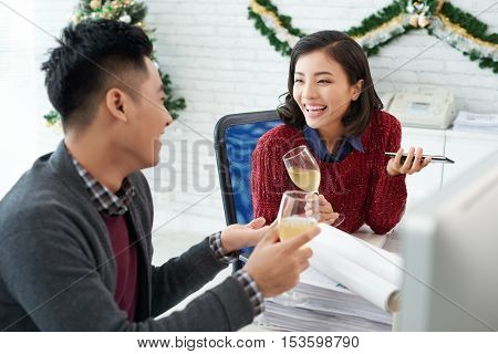 Two Vietnamese colleagues chatting and drinking champagne
