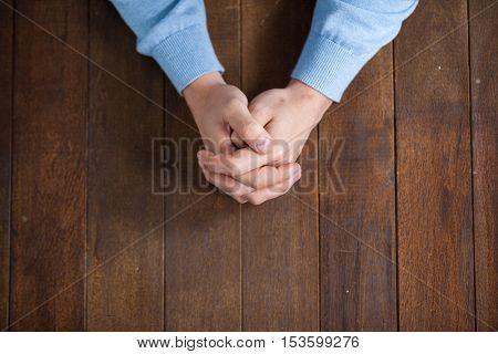 Praying hands of man on wooden desk