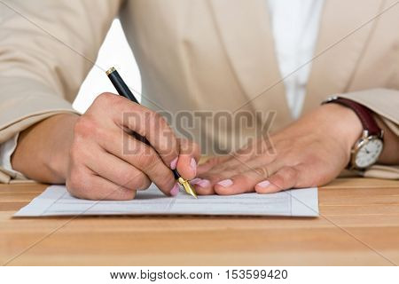 Mid-section of businesswoman filling insurance contract form in office