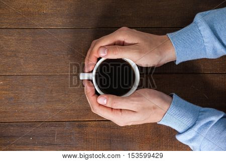 Man holding a cup of coffee on wooden table