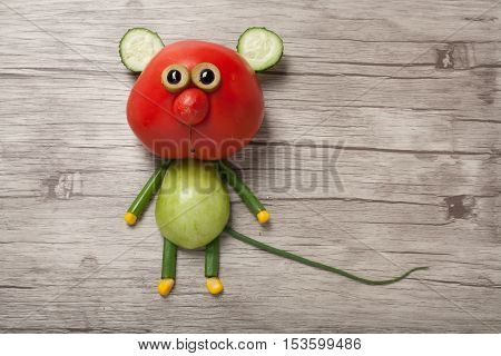 Funny mouse made of red and green tomato on wooden background