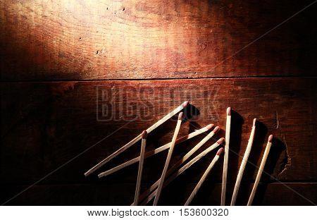 Set of matchsticks on old wooden background under beam of light