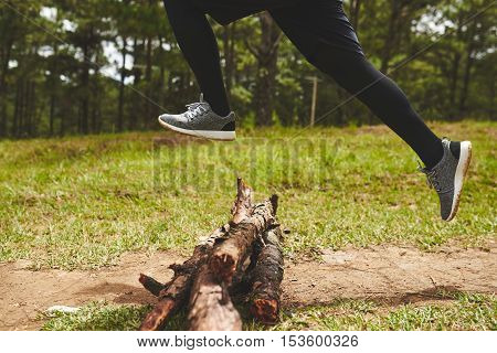 Legs of sportsman jumping over logs in forest