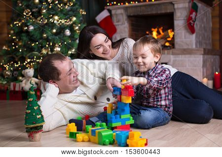 Kid boy and his parents playing with block toys under the christmas tree