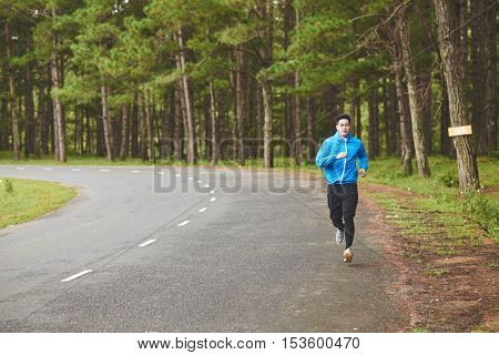 Vietnamese young man jogging along the road