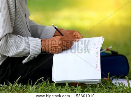 man writes in a notebook on his knee while sitting in the park.