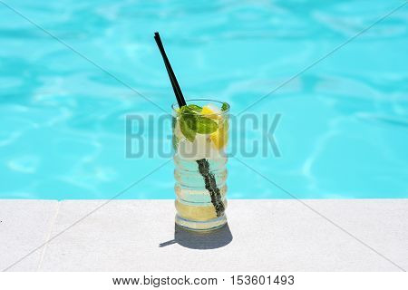 Mojito cocktail near the pool in sunny day