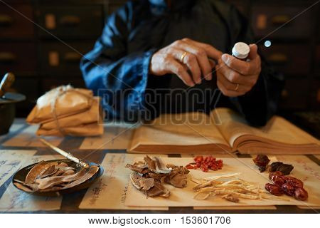 Hands of practitioner making remedy for his patient