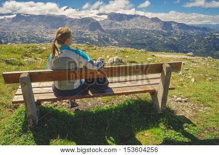 Young female traveller sitting on the bench and enjoying spectacular alpine landscape. Dachstein mountains Austria