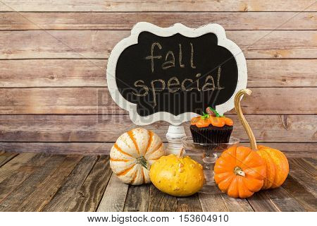 Chalkboard sign with pumpkin muffin and ornamental gourds