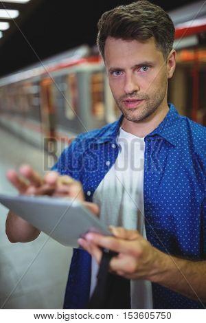 Portrait of handsome man using digital tablet on railway platform