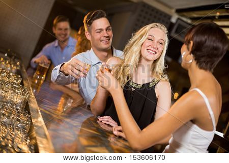 Group of friends toasting a glasses of tequila shot in bar