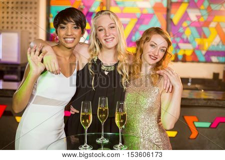 Portrait of smiling female friends standing with arm around in bar and glass of champagne on table