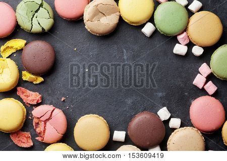 Colorful macaroons on stone table. Sweet macarons. Top view with copy space for your text