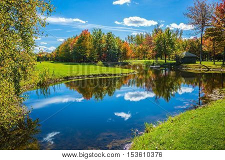 Concept of recreational tourism. The shining sunny day in the French Canada. Park of fantastic beauty. Red, orange and yellow autumn foliage is reflected to clear water of the lake