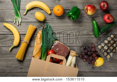 Groceries in paper bag on wooden table top view