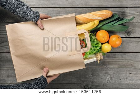 Man's hands holding paper bag of groceries top view