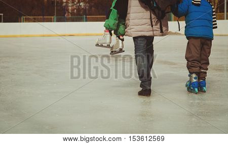 mother with kids skating in winter snow, active family sport