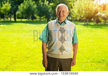 Old guy smiling outdoor. Man on park background. I remembered a funny story. Life is changing so fast.