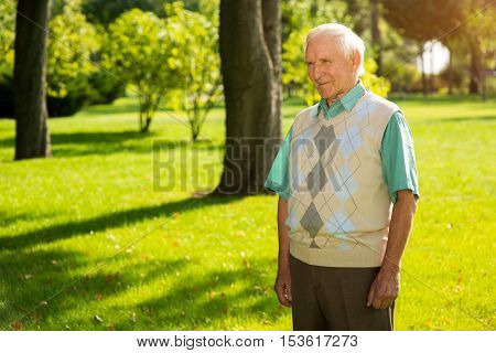 Elderly man standing outdoor. Person slightly smiling. Philosophy of life. Don't regret your choices.