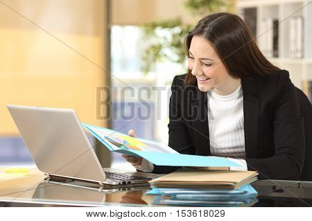 Portrait of a successful beautiful businesswoman reading growth graphics in a paper document at office