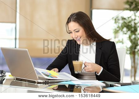 Portrait of an executive working reading growth graphic and drinking coffee in a desk at office