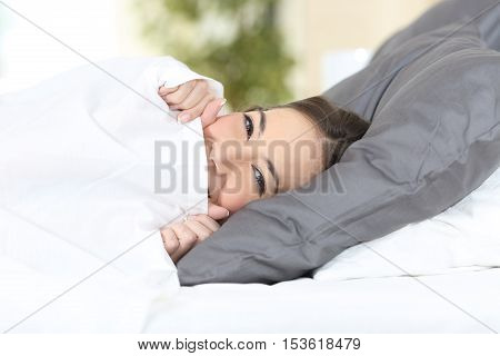 Funny girl resting on a bed covering and hiding face with sheet and looking at camera