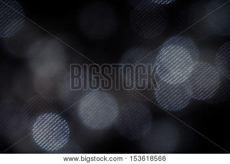 Bokeh dark white mesh circles on black background. Abstract music background.