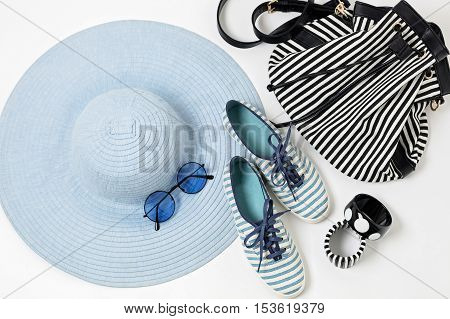 Fashion accessories in blue colors - hat shoes and bag bracelets and glasses.