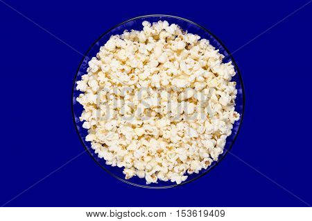 Popped popcorn in a blue glass bowl on blue background. Butterfly shaped popcorn puffed up from the kernels, after it has been heated. Edible and vegan food. Isolated macro photo close up from above.