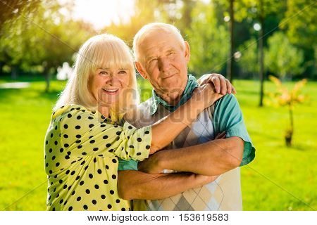 Old couple outdoor. Smiling woman and man. Together after many years. Ties of love are unbreakable.