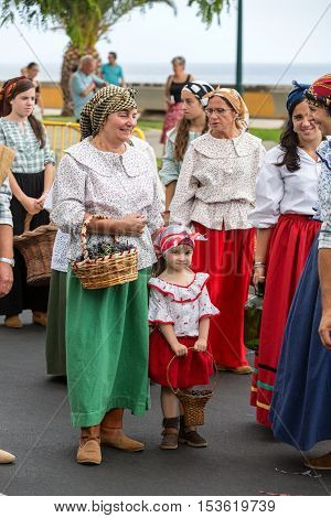 FUNCHAL MADEIRA PORTUGAL - SEPTEMBER 4 2016: the women carry the basket of grapes in traditional costume. Madeira Wine Festival - Historical and Ethnographic parade in Funchal on Madeira. Portugal