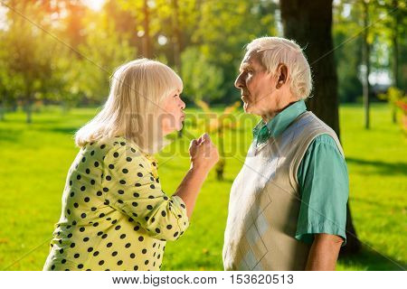 Angry woman and man. Two senior people outdoor. Distrust in relationships. Quarrel of wife and husband.