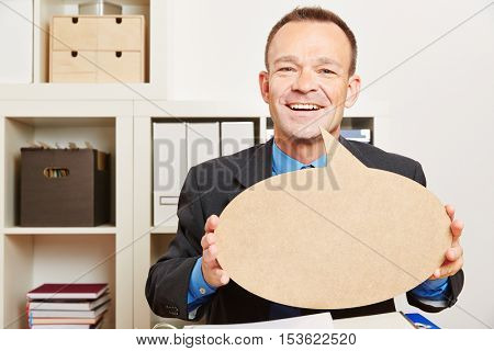 Happy business man in his office with an empty speech bubble